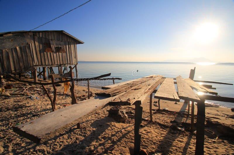 Onvolledige houten planken op een strand naast een blokhuis, die het overzees en de het plaatsen zon onder ogen zien stock afbeelding