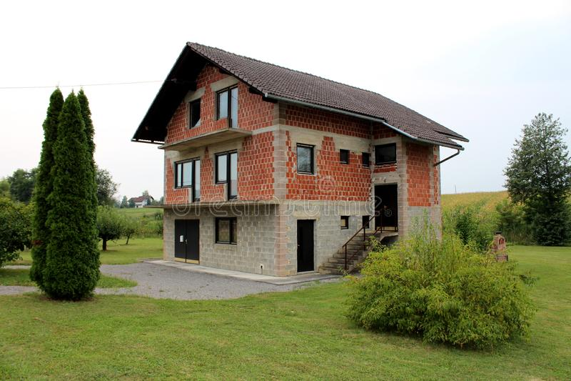Onvolledige rode baksteen en het grijze huis in de voorsteden van de bouwsteenfamilie met nieuwe die deuren en vensters met vers  stock afbeelding