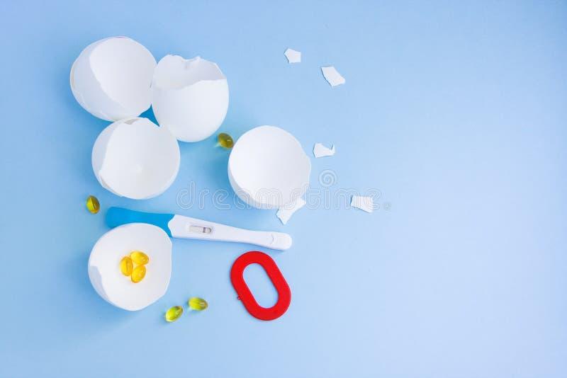 onvruchtbaarheid Negatieve zwangerschapstest, pillen, eierschaal en nummer nul op blauw royalty-vrije stock fotografie