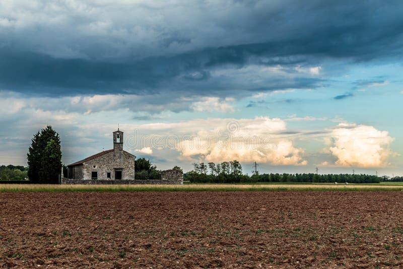 Onweer die een kleine kerk op de gebieden bereiken royalty-vrije stock foto's