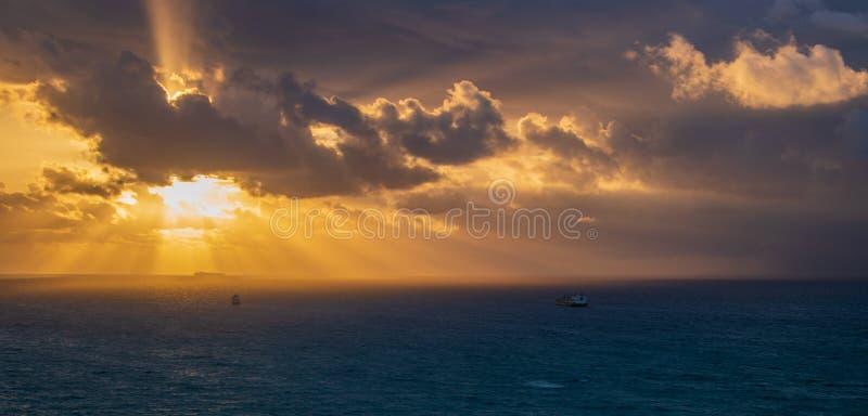 Onweer met dikke donkere wolken die de kust naderen bij zonsopgang De lichtstralen komen uit thewzon achter de donkere wolken, da stock foto's