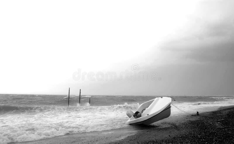 Onweer op het overzees met ten val gebrachte omgekeerde boot op het strand De Zwart-witte foto van Peking, China stock foto