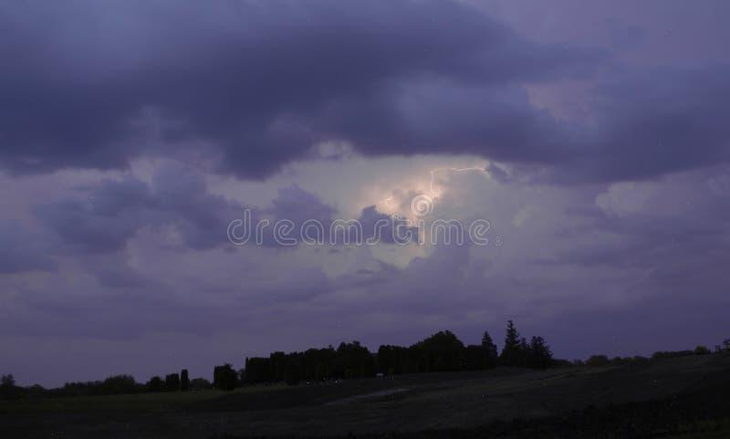 Onweersbui met bliksem in het midden van purpere hemel boven donkere bomen in Minnesota stock fotografie