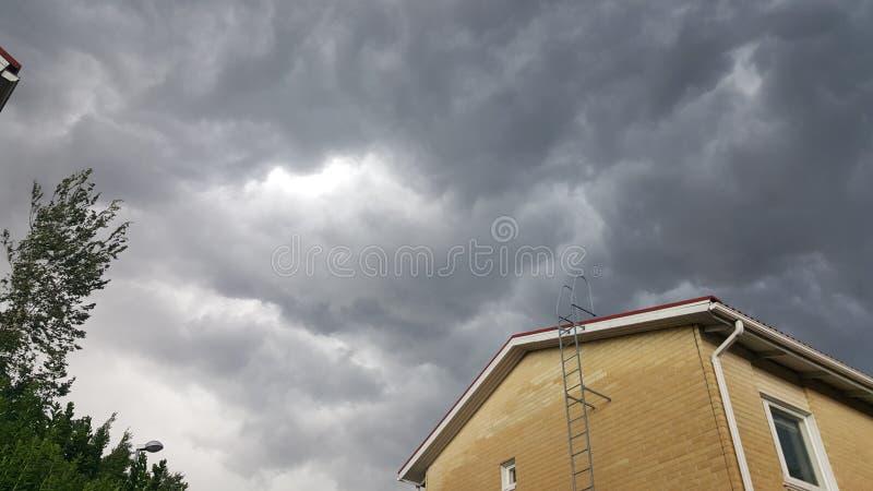 Onweersbui met dark die wolken boven een gebouw bedreigen stock foto