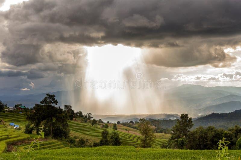 Onweerswolken met regen en zonnestraal stock afbeeldingen