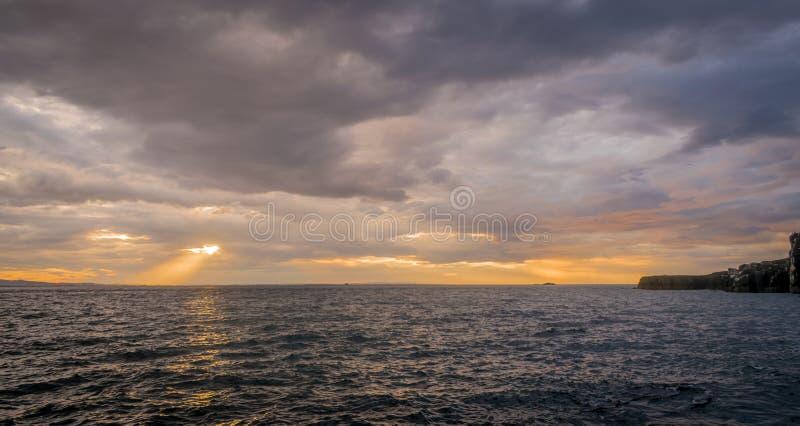 Onweerswolken met zon het plaatsen en zonstralen over de oceaan royalty-vrije stock afbeeldingen