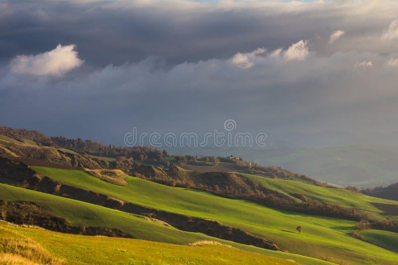 Onweerswolken over de groene heuvels stock afbeeldingen