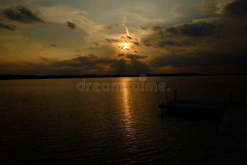 Onweerswolken over het meer als zonreeksen stock afbeelding