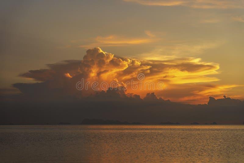 Onweerswolken tijdens zonsondergang Kleurrijke zonsondergang over kalm zeewater dichtbij tropisch strand De vakantieconcept van d stock afbeeldingen