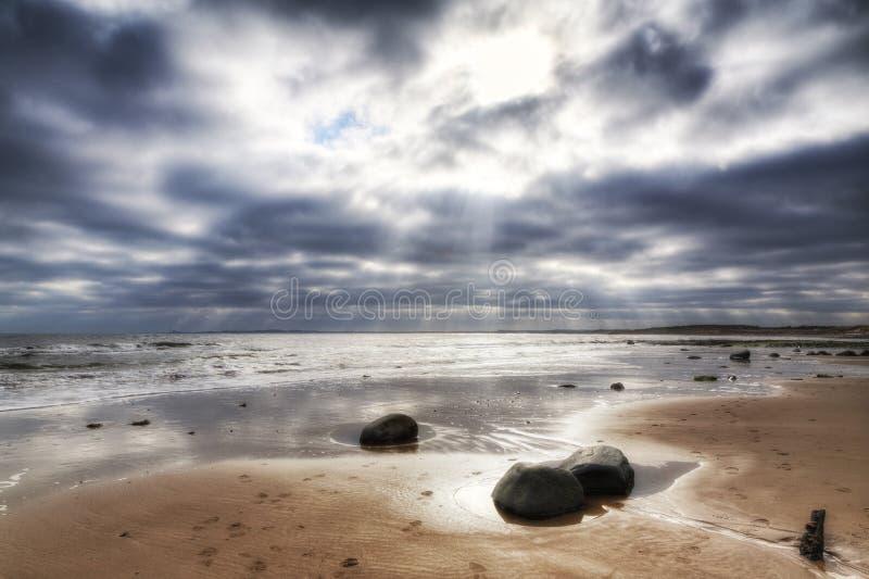 Onweerswolken vóór de rust op een zandig strand stock afbeelding