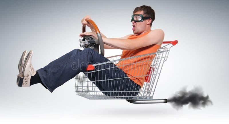 Onwerkelijke gekke bestuurder in een winkelen-kar met wiel stock foto's