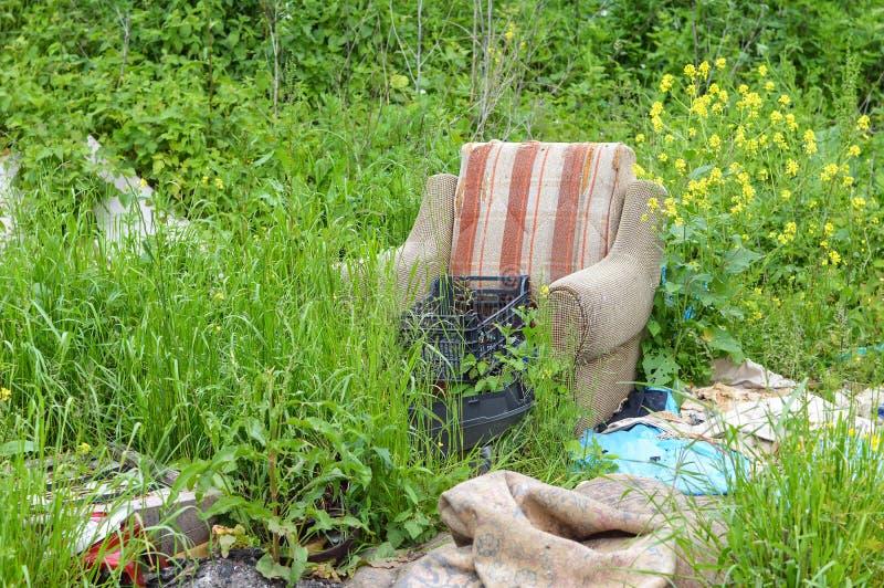Onwettige huisvuilstortplaats in aard Verlaten leunstoel in aard ecologische crisisfoto royalty-vrije stock afbeeldingen