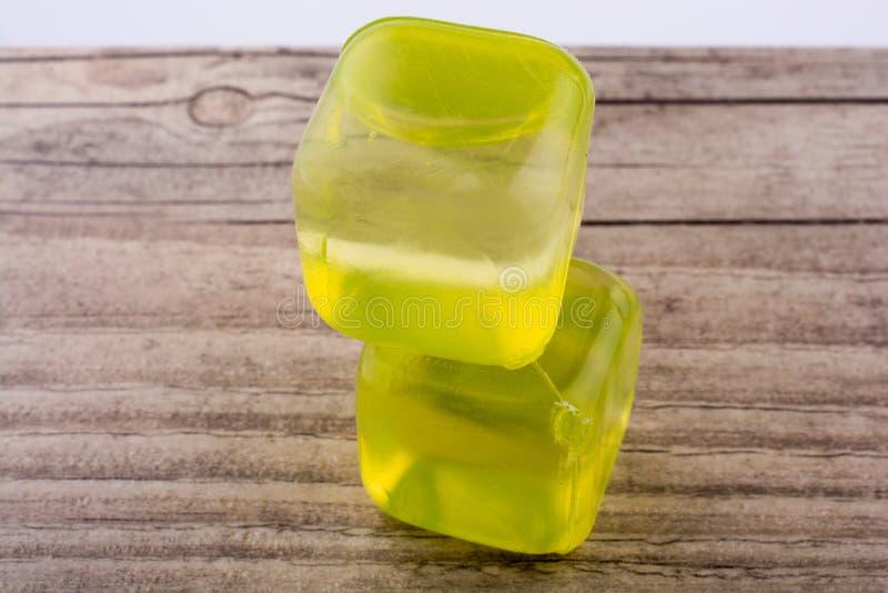 Πλαστοί κίτρινοι κύβοι πάγου στο ξύλο στοκ εικόνα