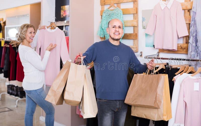 Żony kupienia suknia przy odzież sklepem, mężczyzna zanudza zdjęcia stock