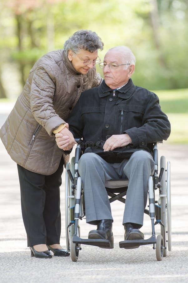 Żony mienia ręki mąż w wózku inwalidzkim obrazy stock