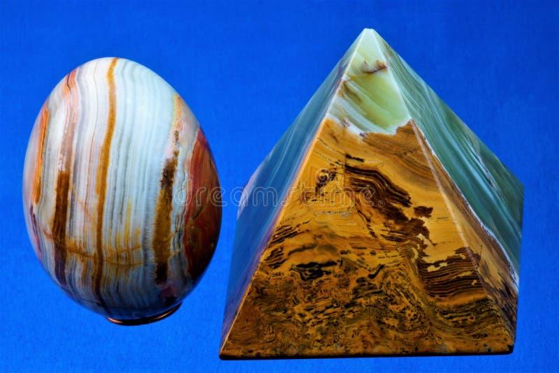 Onyx är en värdefullt och extremt härlig mineral, pyramid och ägg på en blå bakgrund arkivfoton