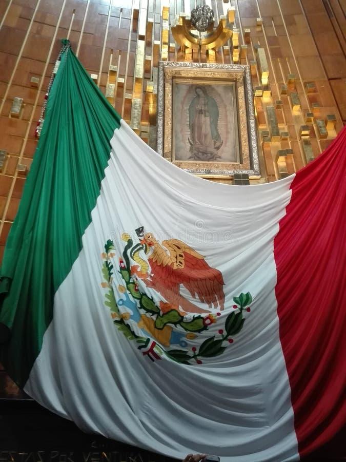 Onze dame van Guadalupe en Mexicaanse vlag stock fotografie