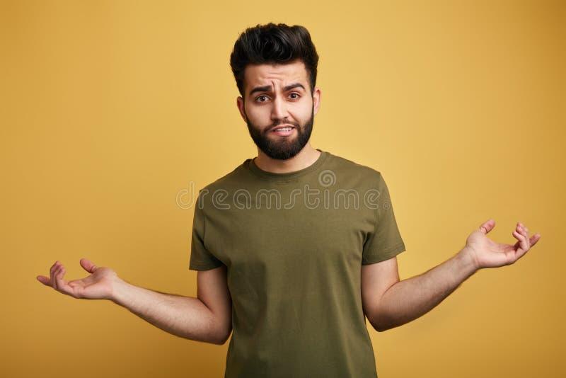 Onzekere twijfelachtige gebaarde mens die groene T-shirt dragen die zijn schouders ophalen stock afbeelding