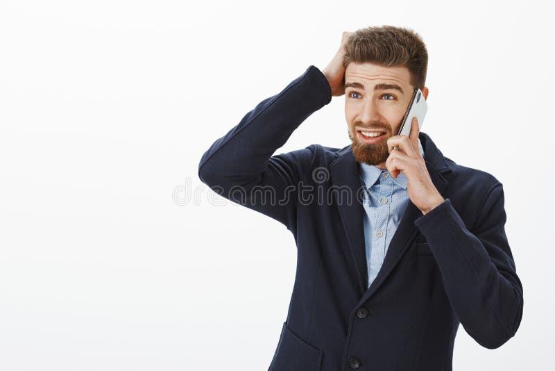 Onzekere verwarde charmante mannelijke ondernemer die in elegant kostuum met baard linker met verontrust gezicht die spreken kijk stock foto