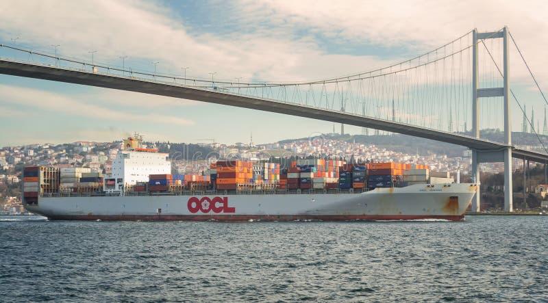 OOCL拥有的被装载的集装箱船通过博斯普鲁斯海峡海峡的东方海外货柜航运公司在博斯普鲁斯海峡,伊斯坦布尔,土耳其下 免版税库存照片