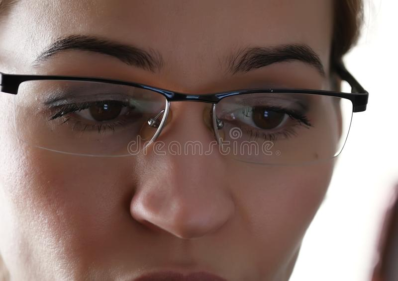 Oog van de close-up het bruine vrouw in glazen Vrouw die een smartphone gebruikt stock afbeelding