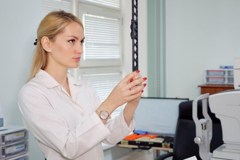 Oogartsvrouw met oftalmologisch apparaat in het kabinet stock afbeeldingen