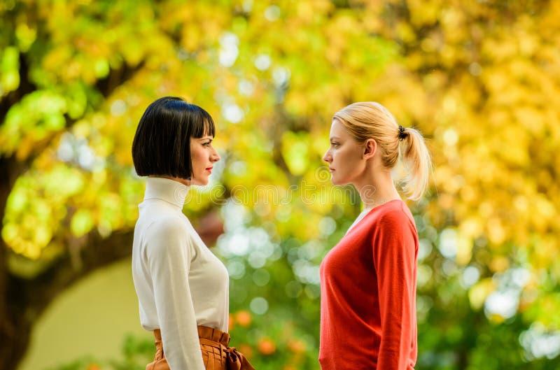 Oogcontact Vrouwen die elkaar met aandacht bekijken Blonde donkerbruine concurrenten Vrouwelijke rivaliteit Vriendschap stock foto