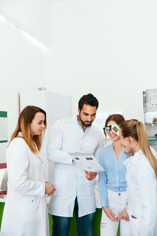 Oogexamen Artsen die Vrouwenzicht met Optometrieglazen controleren stock foto's