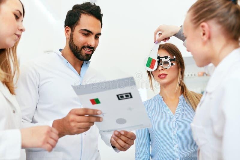 Oogexamen Artsen die Vrouwenzicht met Optometrieglazen controleren stock foto