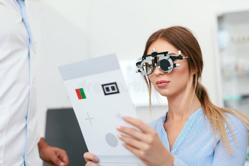 Oogexamen Vrouw die in Optometrieglazen de Kaart van de Oogtest lezen stock afbeelding
