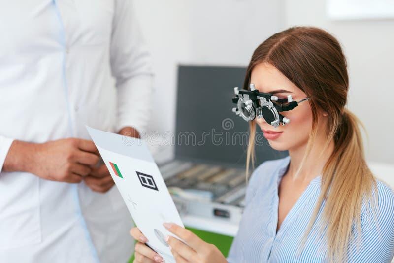 Oogexamen Vrouw die in Optometrieglazen de Kaart van de Oogtest lezen royalty-vrije stock fotografie