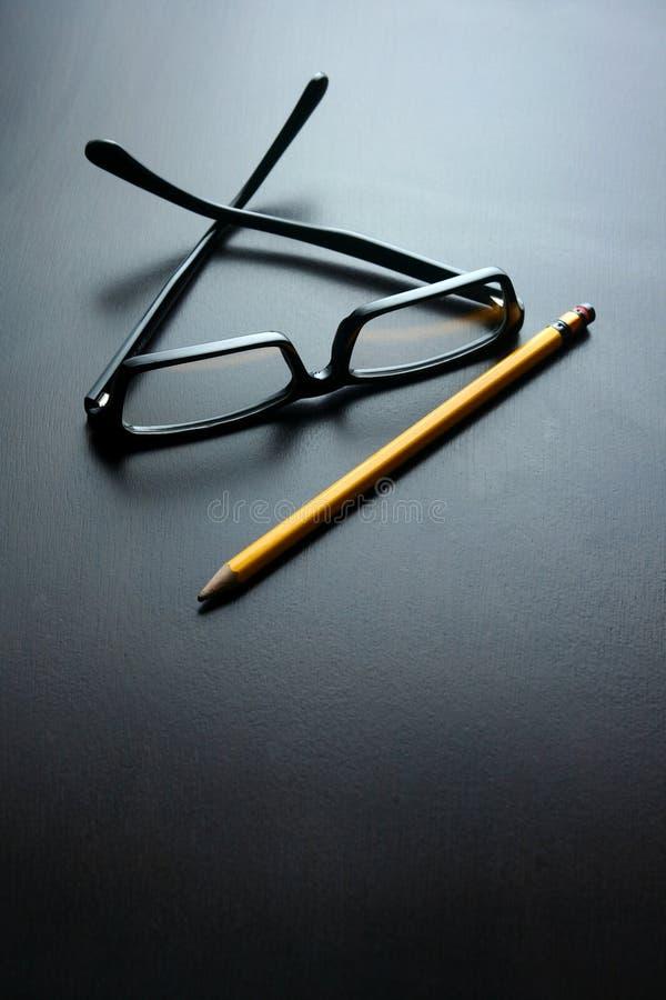 Oogglazen en een potlood op een houten lijst royalty-vrije stock foto's