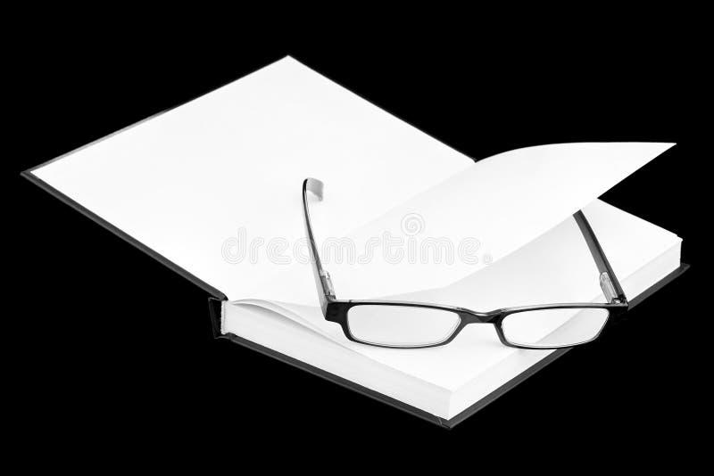 Oogglazen op het boek royalty-vrije stock afbeeldingen