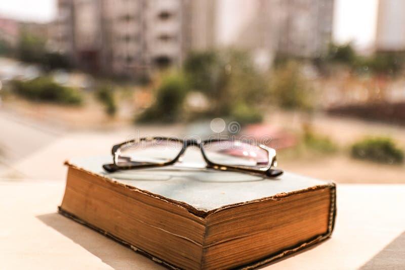 Oogglazen op het oude sjofele boek en de vage achtergrond buiten het venster Onderwijs concept stock fotografie