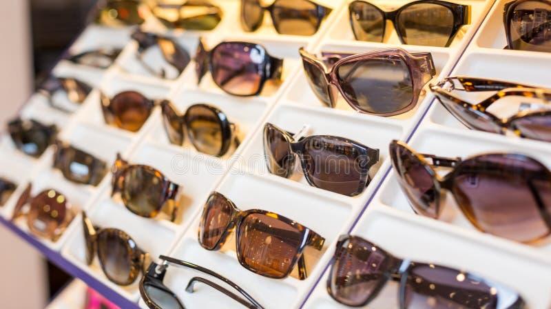 Oogglazen, schaduwen en zonnebril in de winkel van de optometrist stock afbeeldingen