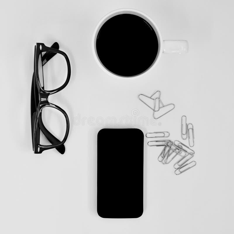 Oogglazen, smartphone, koffie en hart-vormig paperclips op een witte lijst royalty-vrije stock foto's