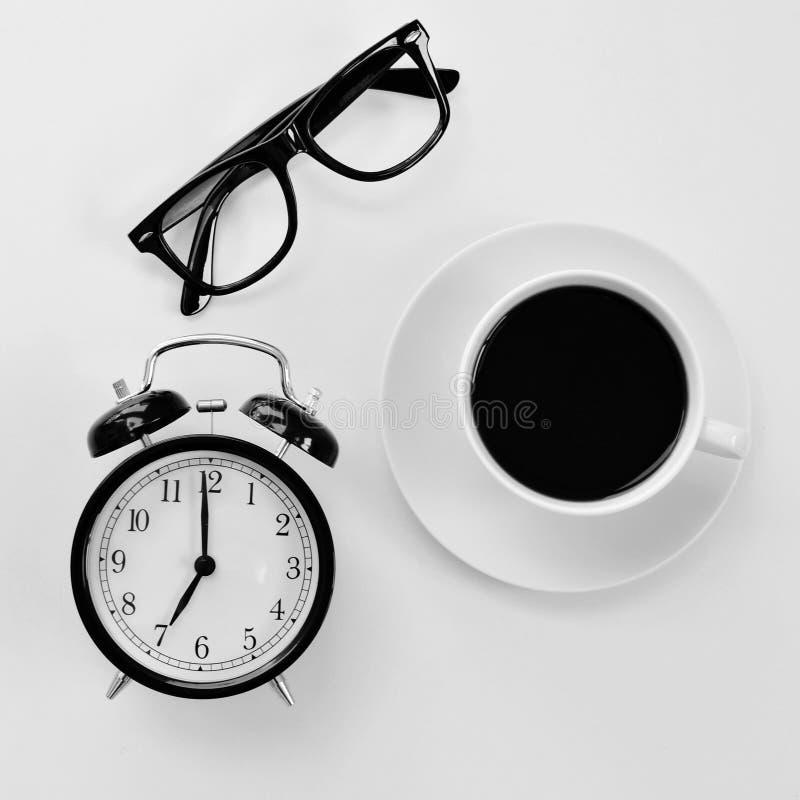 Oogglazen, wekker en koffie stock foto's