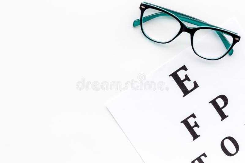 Oogonderzoek De grafiek en de glazen van de zichttest op witte achtergrond hoogste meningsruimte voor tekst stock afbeelding