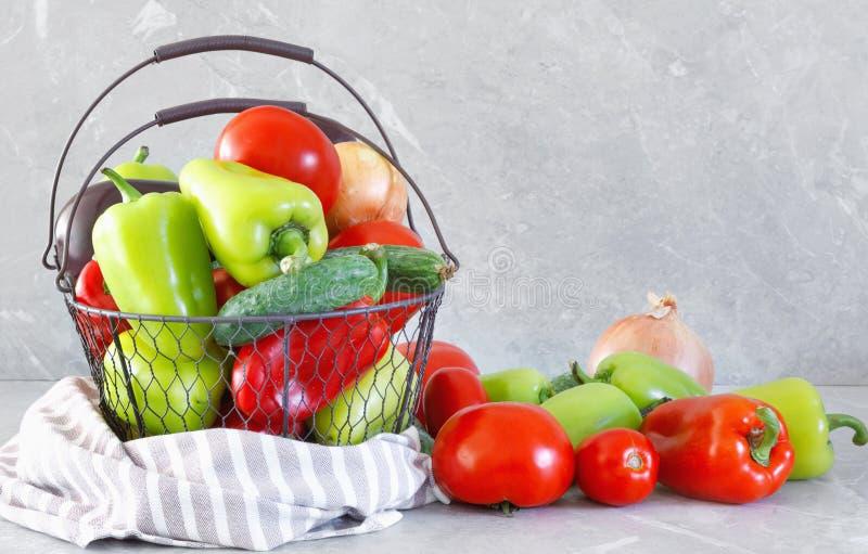 Oogst van rijpe peper, tomaat, aubergine en ui in metaalmand royalty-vrije stock afbeeldingen