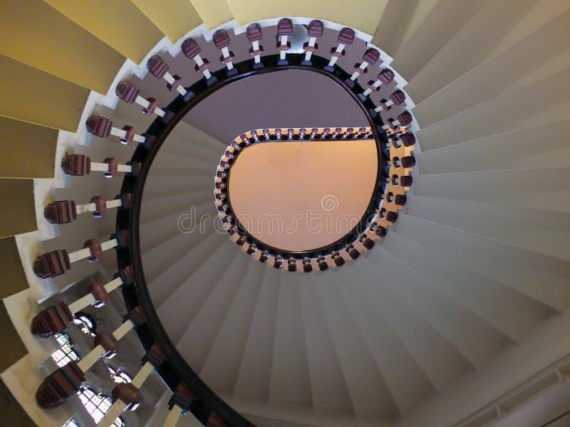 Ooking uppåtriktad sikt av en elegant spiraltrappuppgång med träbannisters i eleganta skuggor av vit arkivbild