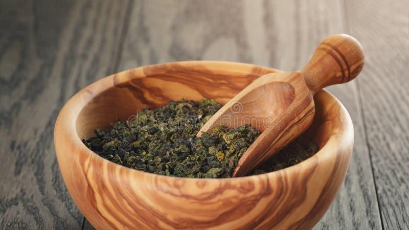 Oolong groene thee in houten kom stock fotografie