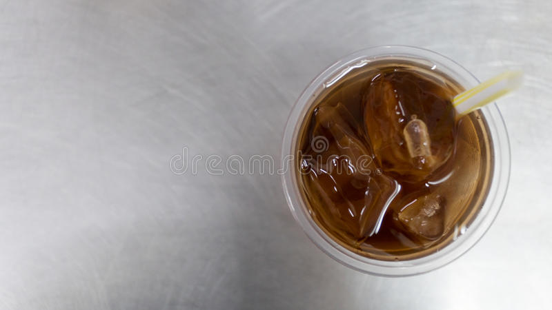 Oolong tea or Chinese tea with ice in plastic glass. Is on the steel table. It& x27;s delicious , good taste , good smell and brown color. Put some ice in to stock photo