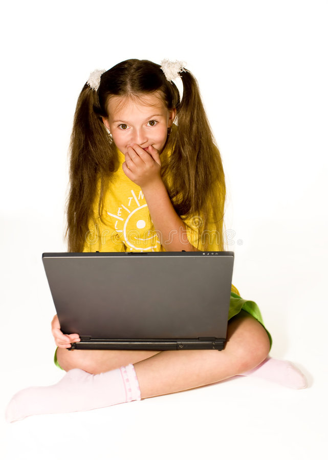 Oops!. Adorable little girl playing on laptop computer royalty free stock image