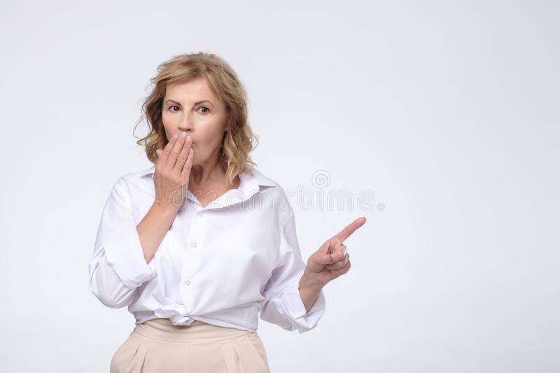 Mature woman feels worried and ashamed, points with index fingers aside. royalty free stock photography