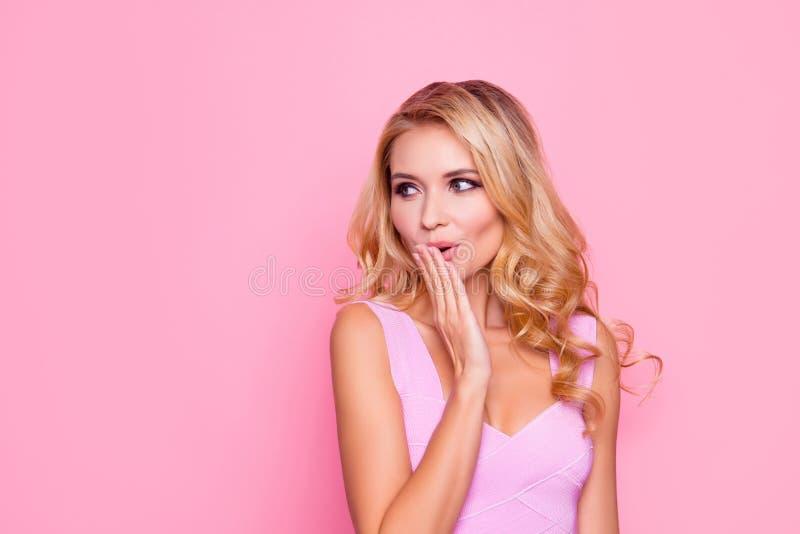 Oops! Feche acima do retrato da menina loura 'sexy', bonita, impressa, surpreendida que guarda sua mão perto da boca, olhando ao  fotografia de stock