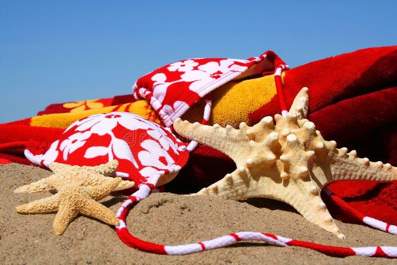 Oops! No bikini top. Bikini top, starfish with beach towel in the sand stock photos