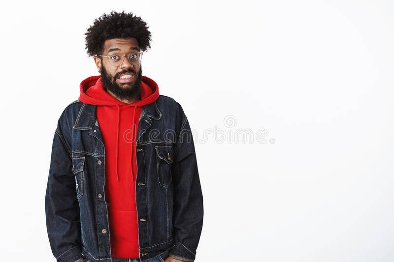 Oops, someone in trouble. Portrait of stunned awkward african american guy clenching teeth in sorry expression raising stock photos