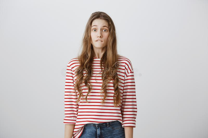 Oops, what have I done. Studio shot of worried beautiful young girl with blonde hair in striped shirt biting lower lip stock photos