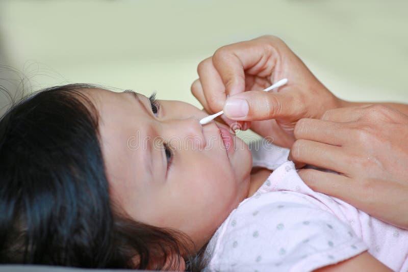 Oor van de moeder het Schoonmakende Baby met katoenen zwabber stock foto