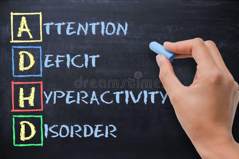 Oordning för hyperactivity för underskott för ADHD-—uppmärksamhet som är handskriven vid kvinnan på svart tavla arkivfoton